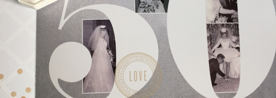 Photo album cover with giant 5 0 with background of black and white wedding photos. Diamond ring box sitting on top of album.